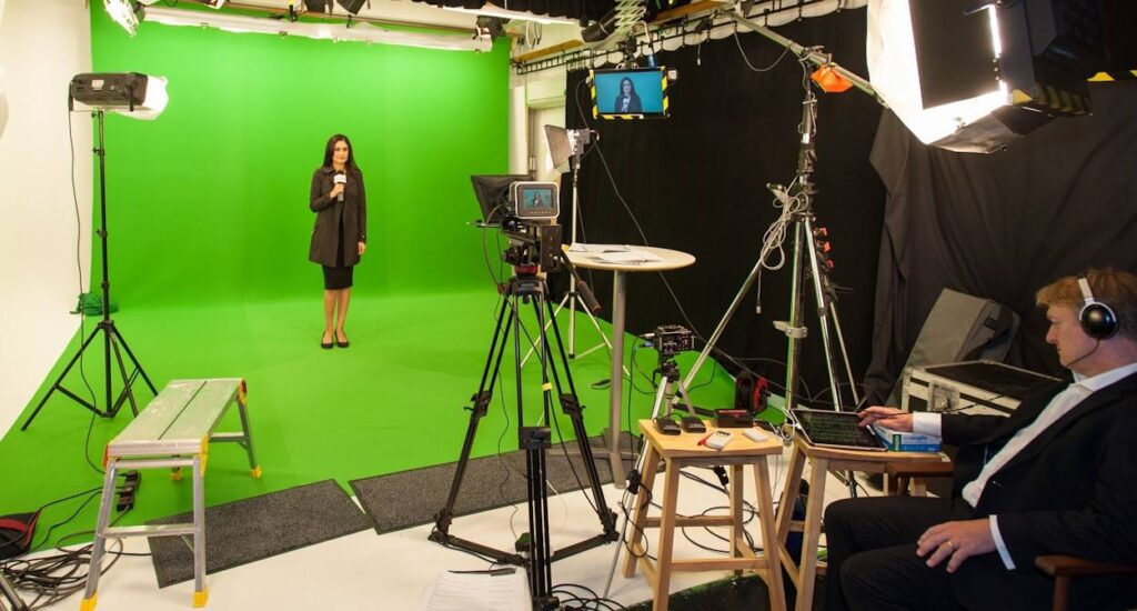 Image of Sheetal Kapoor behind the scenes of a corporate learning and drama filming a video in green screen with autocue
